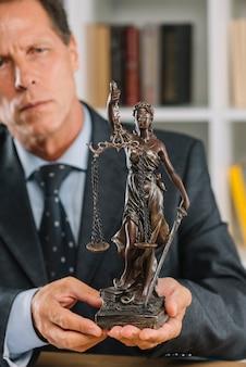 Avvocato maschio maturo che giudica la statua di giustizia a disposizione