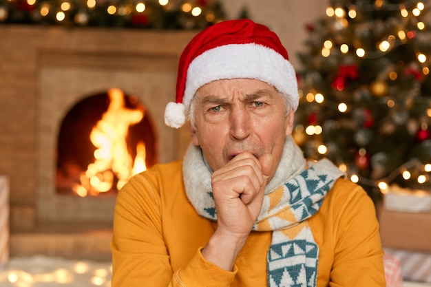 Mature male man in santa hat and yellow sweater coughing,covering mouth, feels bad, posing in festive living room near fireplace. happy new year, celebration, merry holiday at home.