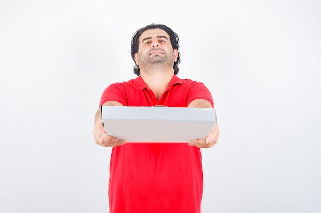 Mature male stretching hands for giving pizza box in red t-shirt and looking confident. front view.