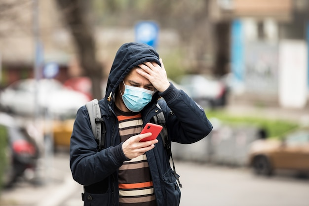 Mature male with phone in hands standing outdoors in protecting medical mask