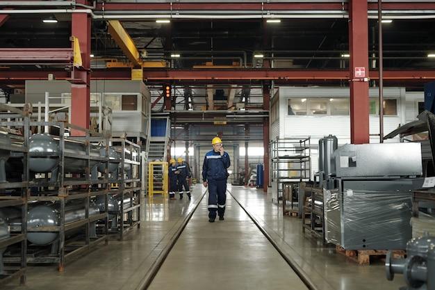 기술 장비를 따라 이동하는 동안 워키토키를 사용하여 작업복 및 보호 헬멧에 산업 공장의 성숙한 남성 노동자