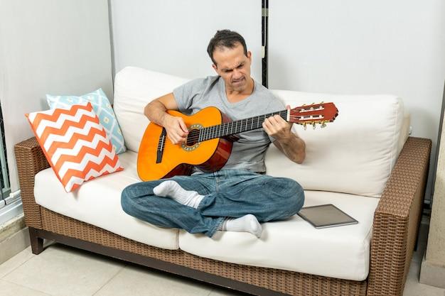 Зрелый мужчина (44 года) играет на гитаре на диване во время карантина из-за вируса короны.