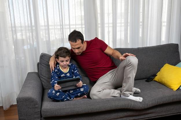 Зрелый мужчина (44 года) сидит рядом с сыном (7 лет) вместе смотрит фильм.