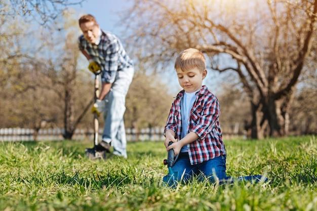 성숙한 남자와 그의 똑똑한 어린 아이가 자연을 돌보고 미래의 과일 나무를 위해 땅에 구멍을 뚫습니다.
