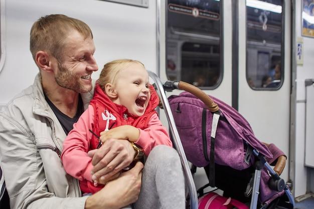 Зрелый мужчина и маленькая эмоциональная девушка пассажиров метро