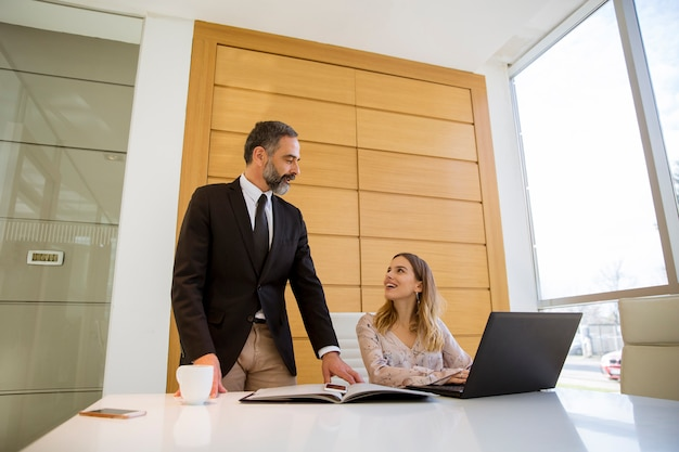 成熟した男と若い女性のビジネスパートナーのオフィスで働くラップトップ