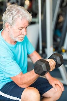 ダンベルを手にベンチに座って体と上腕二頭筋をトレーニングしているジムの成熟した男性-健康でフィットネスのシニアライフスタイル