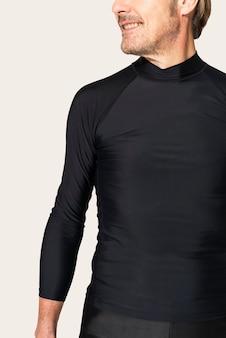 Uomo maturo in rash guard nero e pantaloncini moda mare