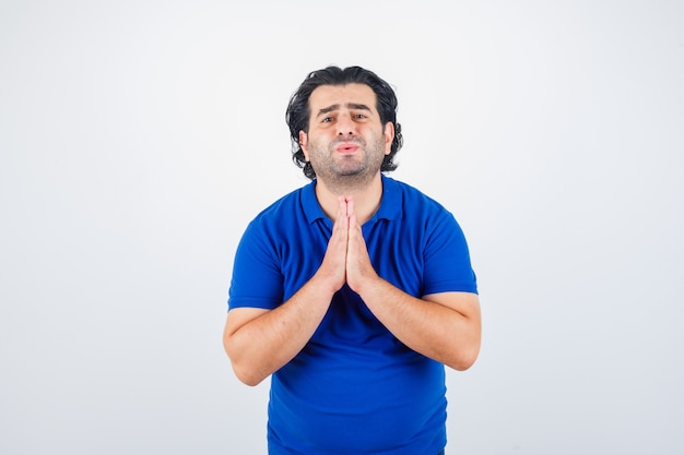 Mature man in blue t-shirt, clasping hands in praying position and looking disappointed, front view.