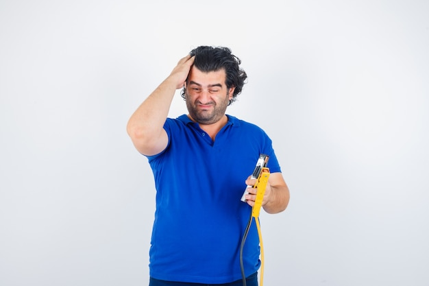 Mature man in blue t-shirt holding construction tools, combing hair with hand and looking thoughtful , front view.