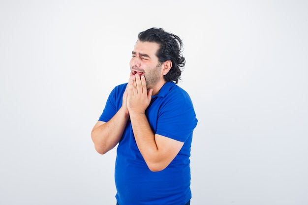 Mature man in blue t-shirt holding hands near mouth and looking mournful , front view.
