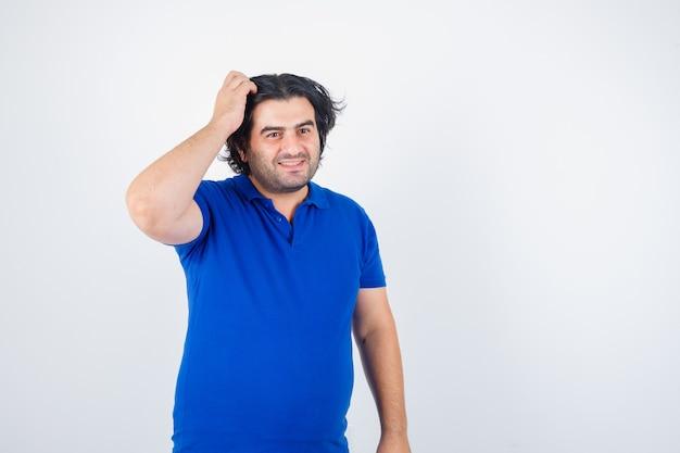 Uomo maturo in maglietta blu, jeans grattandosi la testa, sorridendo e guardando allegro, vista frontale.