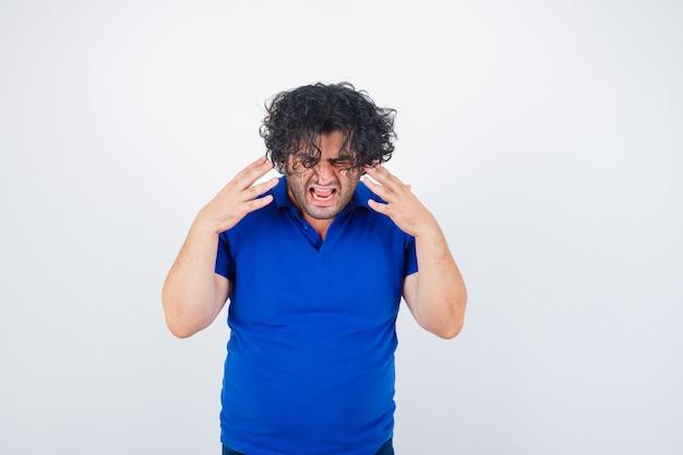 Uomo maturo in maglietta blu alzando le mani in modo aggressivo e guardando malinconico, vista frontale.