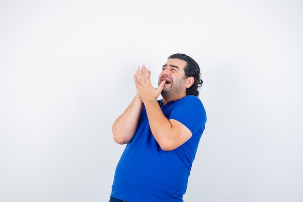 Mature man in blue t-shirt, raising hands in scared manners and looking frightened, front view.
