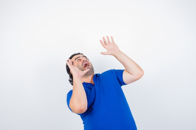 Mature man in blue t-shirt, raising hands in scared manners and looking scared, front view.