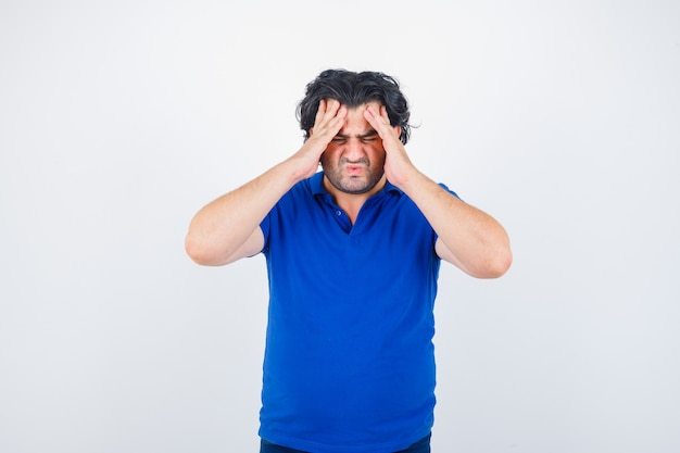 Mature man in blue t-shirt suffering from headache and looking annoyed , front view.