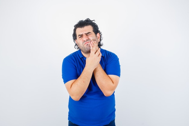 Mature man in blue t-shirt suffering from toothache and looking painful , front view.