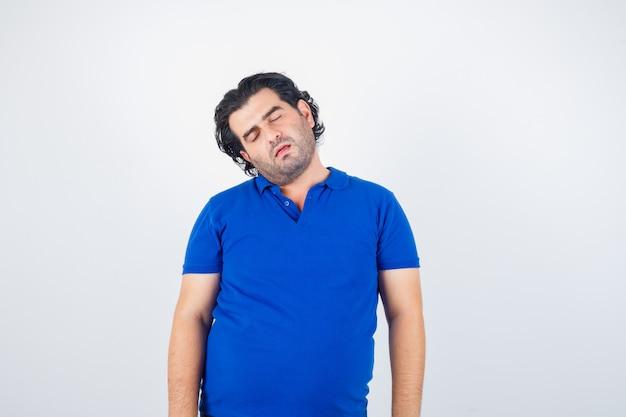 Uomo maturo chinando la testa sulla spalla in maglietta blu e guardando assonnato, vista frontale.