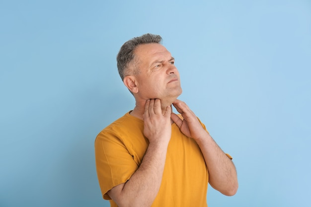 Mature man checking thyroid gland on color background