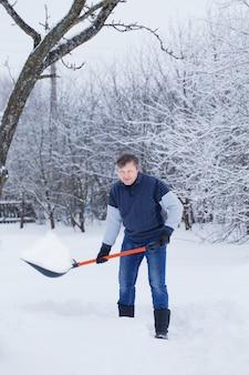 成熟した男は雪のシャベルをきれいに