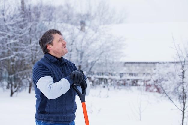 Зрелый мужчина чистит лопату для снега