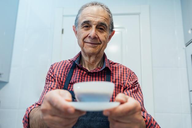 Зрелый мужчина, одетый в клетчатую рубашку и фартук, преподносит чашку с кофе эспрессо