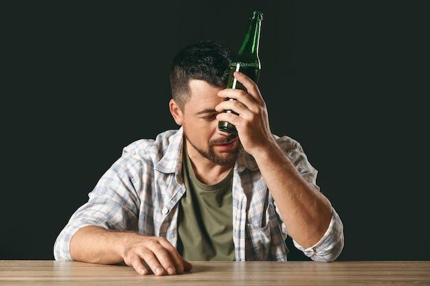 Mature man drinking beer at table