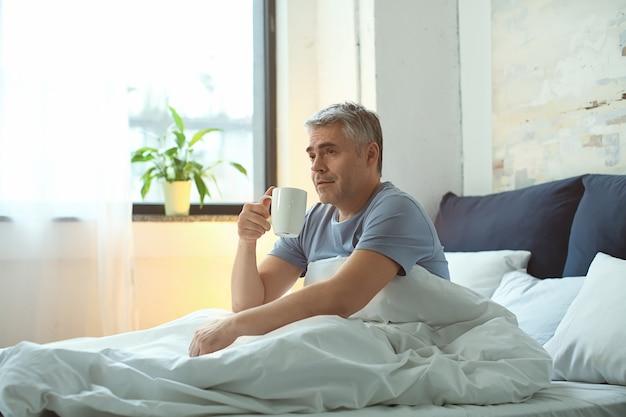 ベッドでコーヒーを飲む成熟した男