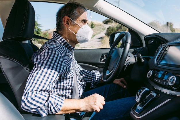 Mature man driving a car with protective mask