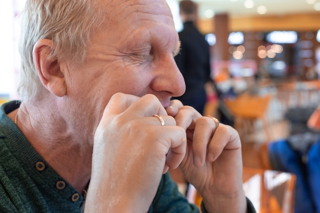 目を閉じて、カフェで手で食べ物を食べる成熟した男