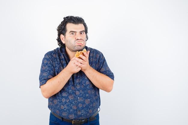 シャツを着たカメラを見て真面目な正面図を見ながらペストリー製品を食べる成熟した男。