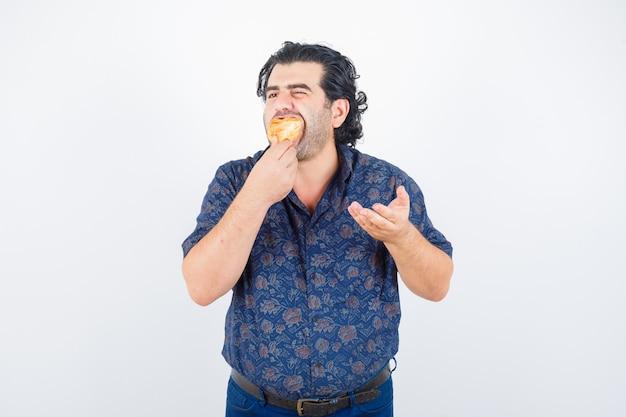 シャツのジェスチャーを質問し、喜んで、正面図を見て手を伸ばしながらペストリー製品を食べる成熟した男。