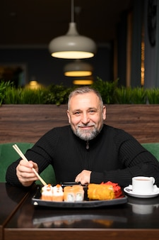 Mature man eating in a sushi restaurant