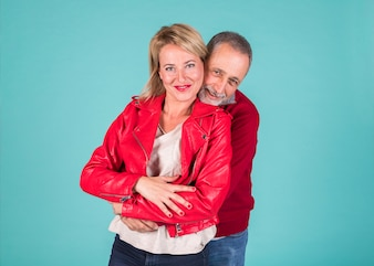 Mature man embracing his smiling wife against colored background