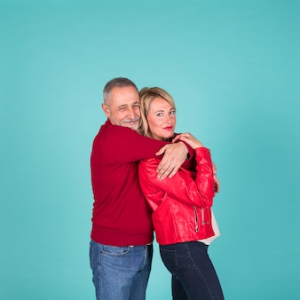 Mature man embracing his wife from behind against turquoise background