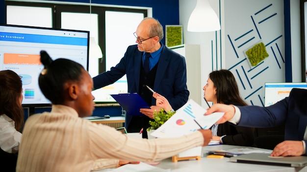 성숙한 남자 기업가가 새로운 프로젝트를 계획하고, 동료에게 브리핑을 하고, 브레인스토밍 중에 회사 전략을 설명합니다. 회의 중 전문 스타트업 금융 사무실에서 일하는 다양한 팀