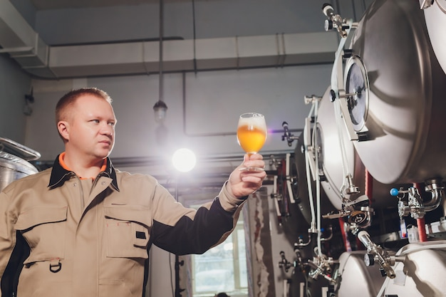 Mature man examining the quality of craft beer at brewery. inspector working at alcohol manufacturing factory checking beer. man in distillery checking quality control of draught beer.