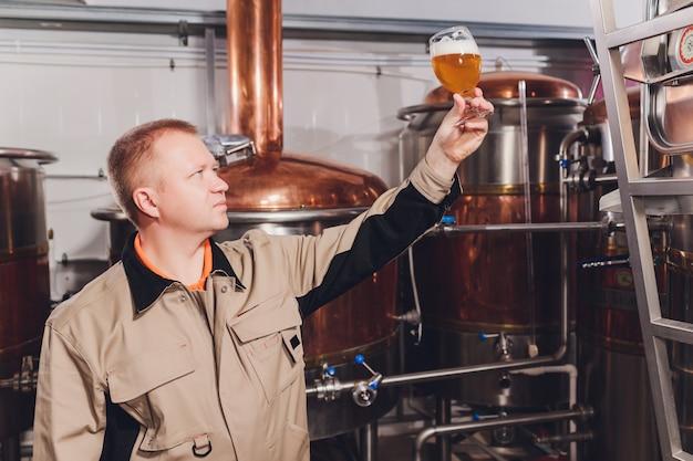 醸造所でクラフトビールの品質を調べる中年の男性。アルコール製造工場で働く検査官がビールをチェックします。生ビールの品質管理をチェックする蒸留所の男。
