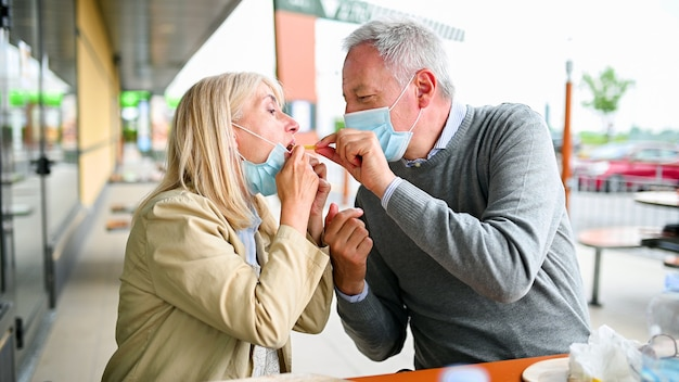 Mature man feeding a french fry to his wife during coronavirus times