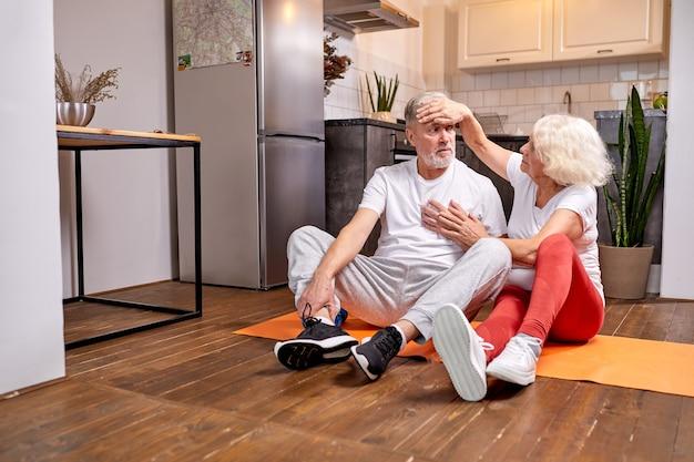 성숙한 남자는 신체 활동, 여성 지원 및 도움 후 기분이 좋지 않으며 요가 후 바닥에 앉아 있습니다.