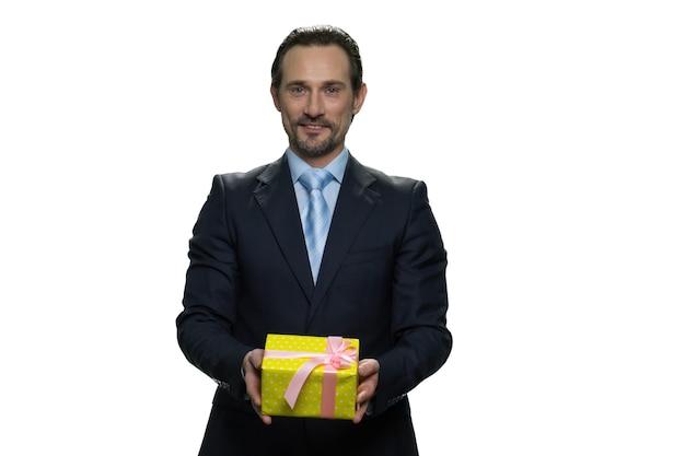 성숙한 남자는 노란색 선물 종이에 싸서 선물을 제공합니다. 흰 벽에 고립 된 중 년 사업가입니다.