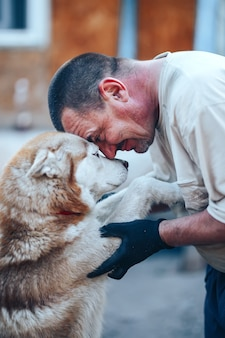 Mature man in gloves hugging red husky dog forehead to forehead, eyes o eyes, care friendship concept