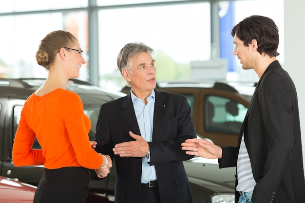 Mature man handshaking with young couple and auto in car dealership