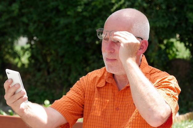 成熟した男は彼のスマートフォンで読書するために彼の視力に問題があります