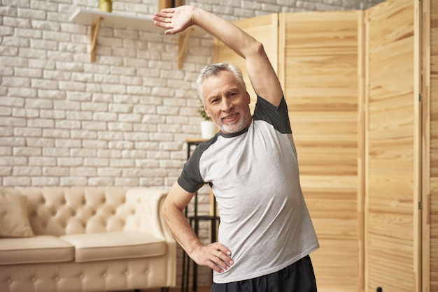 Mature man healthy spine pensioner sports at home.
