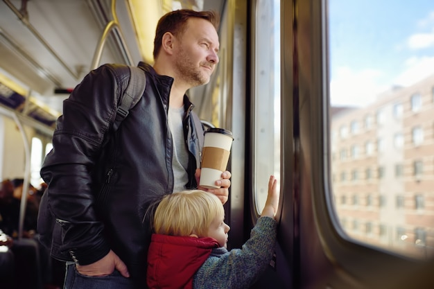 Mature man and his little son looks out the window of the car in the subway in new york.