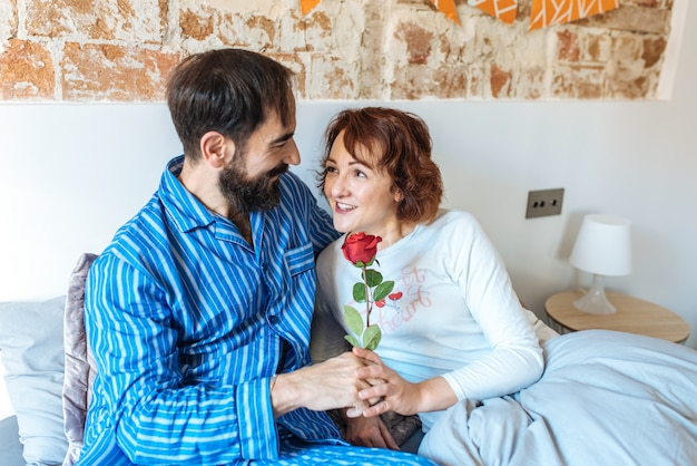 Mature man on his pajamas giving a rose on valentines day to her wife relaxed at home in bed