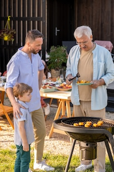 Mature man his son and grandson making grilled corn for family dinner