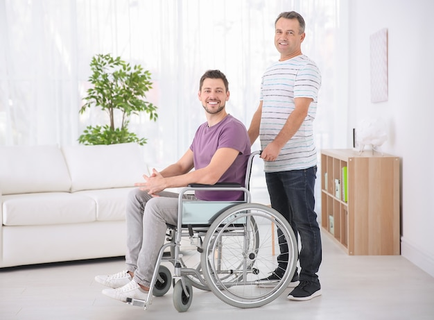 Mature man and his son in wheelchair indoors