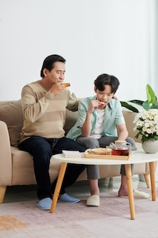 Mature man and his teenage son enjoying tea and potato chips when having short break after working and studying